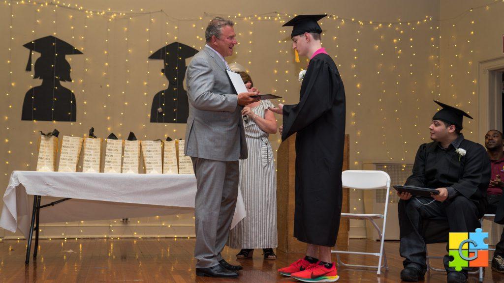 Kevin Gersh Handing a Diploma to a Gersh Academy Graduate