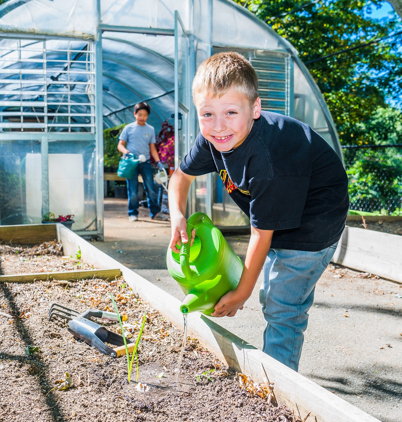 West Hills Academy Student Watering Plants in the Greenhouse